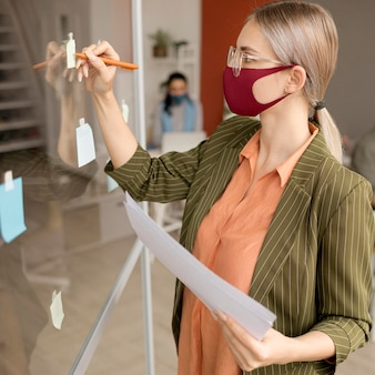 Ritratto di donna che indossa la maschera per il viso al lavoro