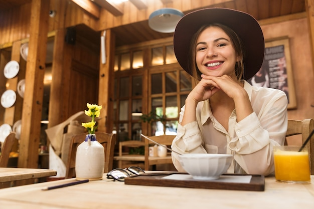 Portrait of woman wearing hat drinking orange juice, while sitting in restaurant