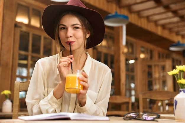 Portrait of woman wearing hat drinking orange juice, while sitting in stylish cafe