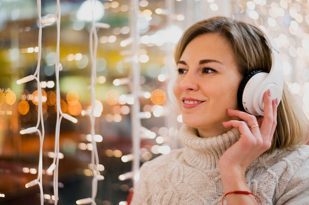 Portrait of woman wearing headphones near christmas lights
