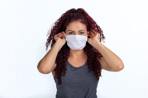 Portrait of a woman wearing or removing her face mask in times of pandemic. isolated on a white background.