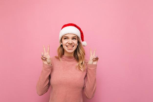 Portrait woman wearing santa hat listening to music in wireless headphones