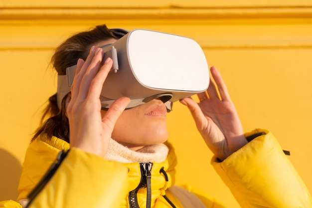 Portrait of a woman wearing virtual reality glasses on the street against a yellow wall in bright sunlight in winter in warm clothes