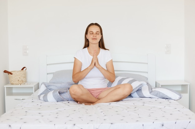 Portrait of woman wearing white casual style t shirt and shorts, sitting on bed in light bedroom, doing yoga practice and meditating, keeping palms together and closed eyes.