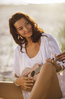 Portrait of woman in white dress with ukulele sitting down on the sand of the beach