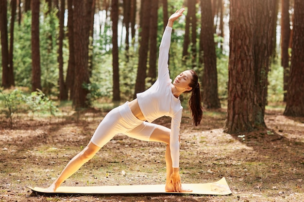 Portrait of woman in white stylish sport top and leggins standing on mat in yoga position in beautiful forest, stretching body, practicing yoga outdoors.