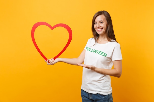 Portrait of woman in white t-shirt with written inscription green title volunteer hold big red wooden heart isolated on yellow background. voluntary free assistance help, charity grace work concept.