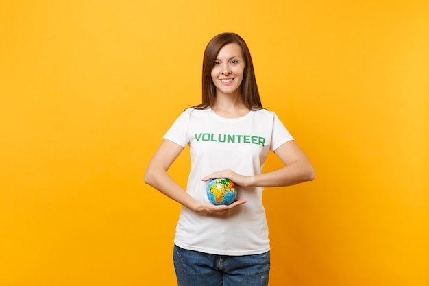 Portrait of woman in white t-shirt with written inscription green title volunteer hold in palms earth world globe isolated on yellow background. voluntary free assistance help, charity grace concept.