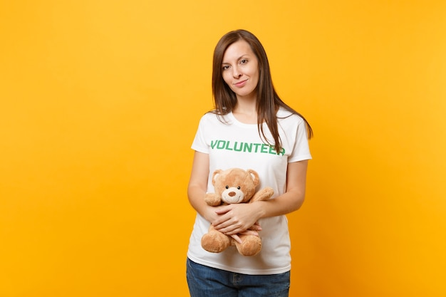Portrait of woman in white t-shirt with written inscription green title volunteer hold teddy bear plush toy isolated on yellow background. voluntary free assistance help, charity grace work concept.