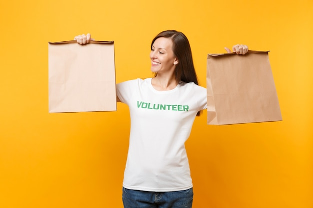 Portrait of woman in white t-shirt written inscription green title volunteer hold blank craft paper bag for takeaway isolated on yellow background. voluntary free assistance help charity grace concept