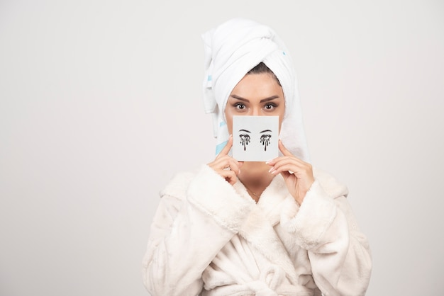 Ritratto di donna in un asciugamano bianco con la tavolozza di ombretti