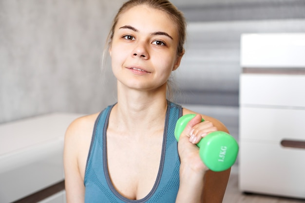 Portrait of a woman who holds a dumbbell in her hands in a bright room