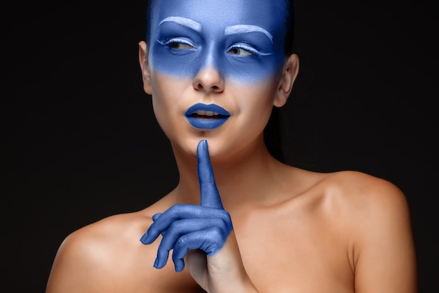 Portrait of a woman who is covered with blue paint
