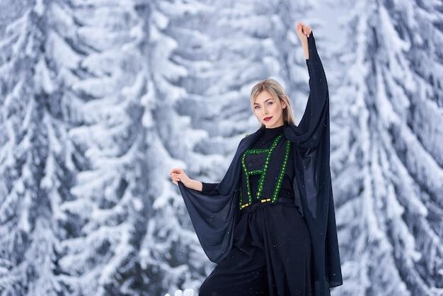 Portrait of woman on winter day on snowy landscape background
