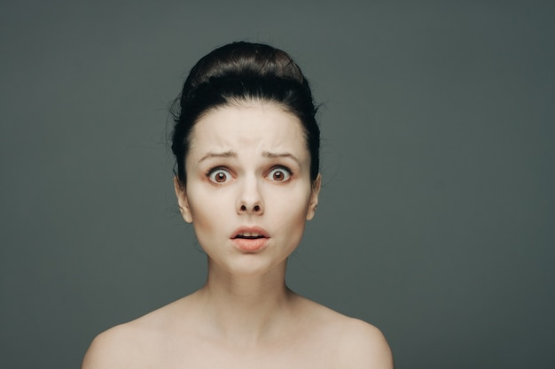 Portrait of a woman with bare shoulders emotions gathered hair