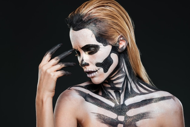 Portrait of woman with blonde hair and halloween skeleton makeup over black background