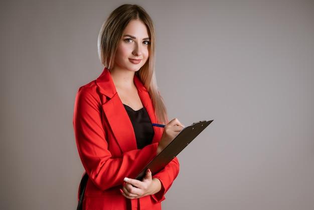 태블릿에 펜으로 쓰는 빨간 재킷에 금발 머리를 가진 세로 여자