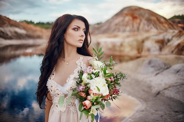 Портрет женщины с голубыми глазами и букетом цветов в руках на природе. шикарные волосы и идеальная кожа, красивый естественный макияж. девушка с букетом роз, таинственный образ мечты женщины