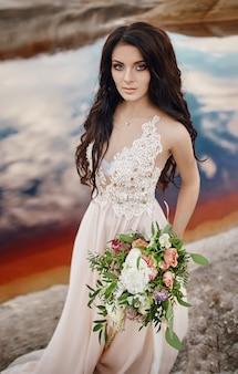 自然に青い目と彼女の手に花の花束を持つ肖像画の女性。ゴージャスな髪と完璧な肌、美しいナチュラルメイク。バラの花束を持つ少女、不思議な夢のイメージの女性
