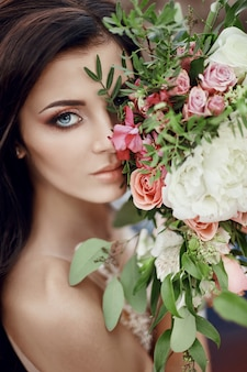 Portrait woman with blue eyes and bouquet of flowers in her hands on nature