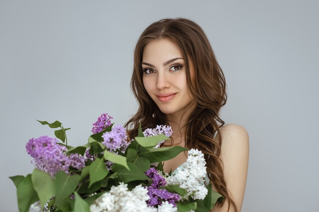Portrait of the woman with a bouquet of spring flowers
