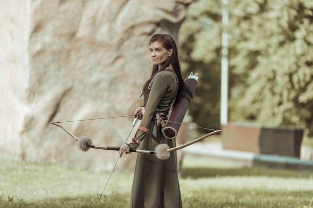 Portrait of woman with bow and arrow on blurred background