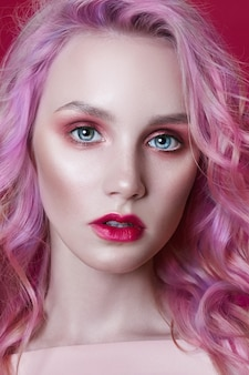 Portrait of a woman with bright colored flying hair, all shades of pink purple. hair coloring, beautiful lips and makeup. hair fluttering in the wind. sexy girl with long hair