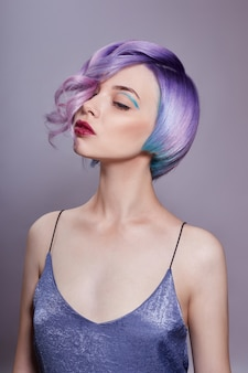 Portrait of a woman with bright colored flying hair, all shades of purple. hair coloring, beautiful lips and makeup. hair fluttering in the wind. sexy woman with short  hair. professional coloring