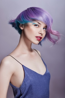 Portrait woman with bright colored flying hair, all shades of purple. hair coloring, beautiful lips and makeup. hair fluttering in wind