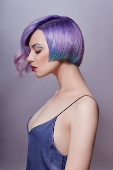 Portrait of a woman with bright colored flying hair, all shades of purple. hair coloring