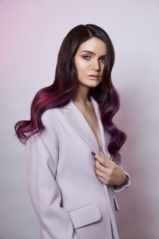 Portrait of a woman with bright colored flying hair, all shades of purple. shiny healthy colored hair coloring, beautiful lips and makeup. sexy girl with long hair styling