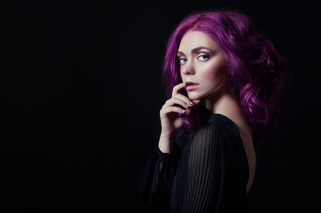 Portrait of a woman with bright purple flying hair