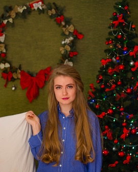 Portrait of a woman with bright red lips, blond long hair against the new year tree. young woman with a white pillow in his hands