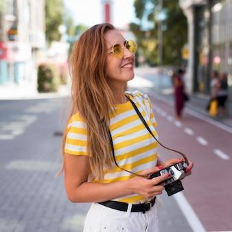 Ritratto di donna con fotocamera in città