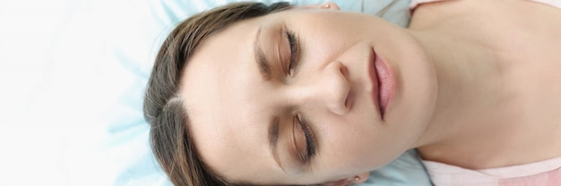 Portrait of woman with closed eyes lying in bed causes of insomnia in women concept