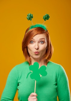 Portrait of woman with clover shaped banner blowing a kiss