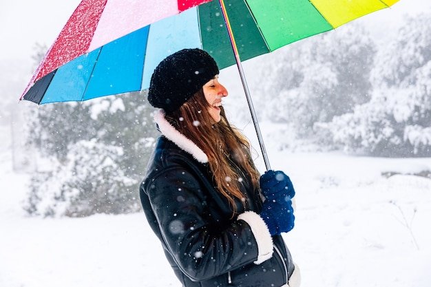Portrait of a woman with a colorful umbrella happy during a snowfall.