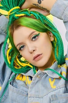 緑と黄色の髪を創造的に染めたポートレート女性。カラフルな明るいドレッドヘア、美しいモダンなメイク