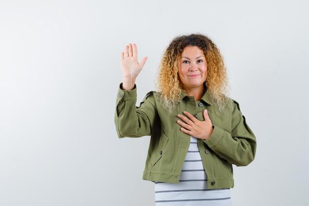 Ritratto di donna con capelli biondi ricci che mostra il palmo, tenendo la mano sul petto in giacca verde e guardando riconoscente vista frontale
