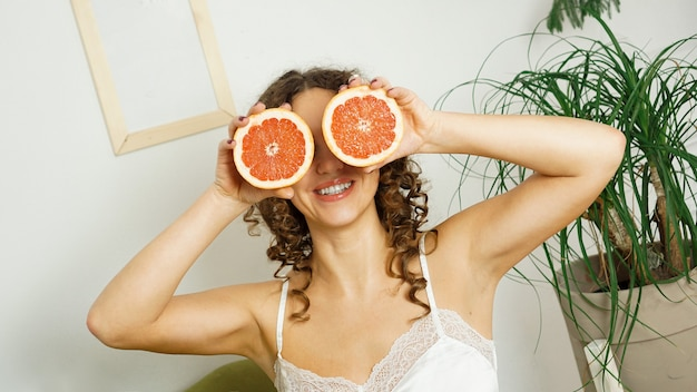 Portrait of woman with curly hair covering her eye with grapefruit at home - light room with green plants. the concept of happiness, beauty and health