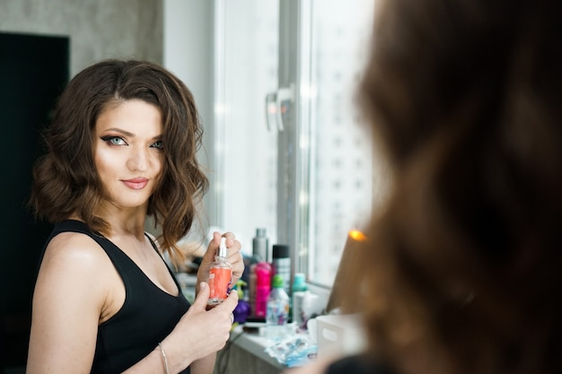 Portrait of woman with curly hair looking at reflection in mirror