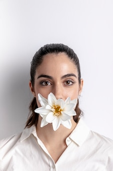 Portrait of woman with flower covering mouth