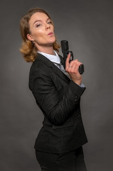 Portrait of woman with gun on grey background