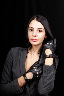 The portrait of the woman with hands in black leather gloves no fingers  on the black space.