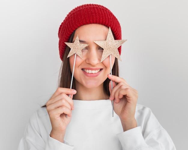 Ritratto di donna con cappello tenendo decorazioni a stella