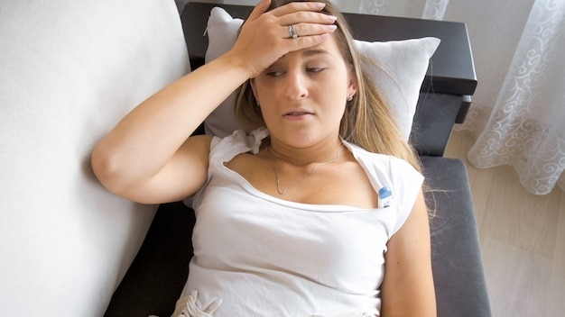 Portrait of woman with headache or high temperature lying on sofa and holding hand on forehead