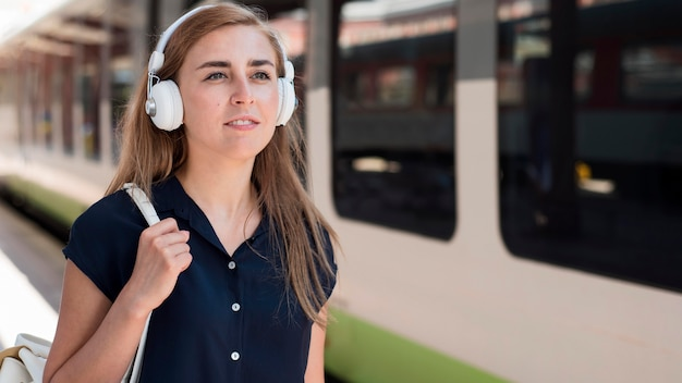 Portrait of woman with headphones in train station