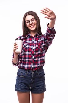 Ritratto di donna con gesto ciao bere tè o caffè dal bicchiere di carta su bianco.