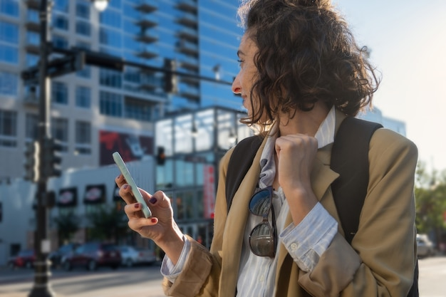 Portrait of woman with jacket, backpack and cell phone in hand in city, concept new beginnings, with copy space.