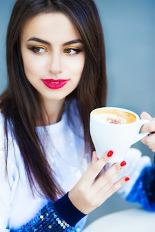 Portrait of a woman with long hair drinking a coffee